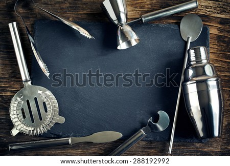 Set of bar accessories and ingredients for making a cocktails arranged on a wooden background with black board for copy space
