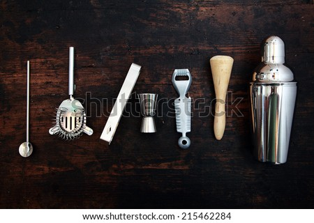Set of bar or pub accessories with a martini cocktail shaker arranged in a neat line on a black background
