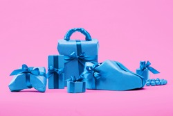 Set of beautifully wrapped blue gift boxes on a pink colored background. Christmas photo.