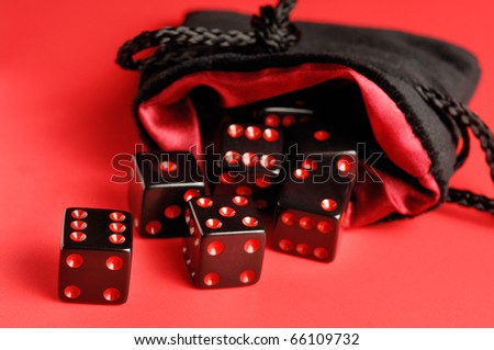Set of black dice in a pouch isolated on red background