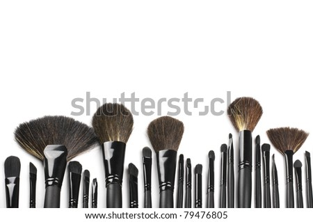 Set of black make-up brushes in row on white background as border.