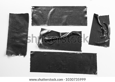 Set of black tapes on white background. Torn horizontal and different size black sticky tape, adhesive pieces.