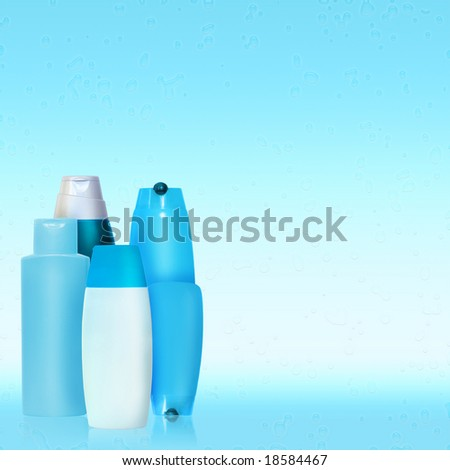set of blue cosmetic bottles over blue background with water drops. copyspace is left for your text