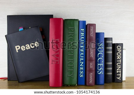 Set of books on a wooden shelf with written titles: Peace, Love, prosperity, fruitfulness, management, success, opportunity, strategy, planning. #1054174136