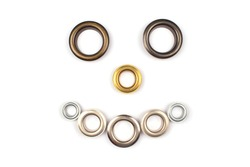 Set of brass multicoloured metal eyelets or rivets - curtains rings for fastening fabric to the cornice, isolated on white background with copyspace for text. Catalogue photo, selective focus