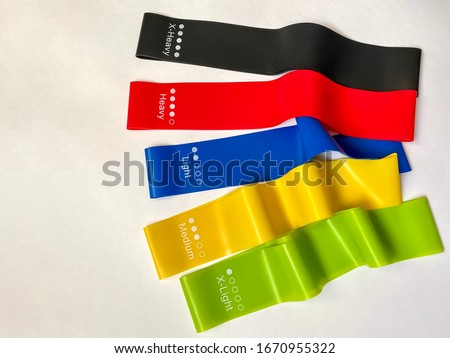 Set of bright multi-colored latex rubber bands for fitness on a white background.  sports concept.  fitness trend.  top view, flat lay, copy space. Photo stock ©