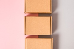 Set of brown cardboard boxes on pink and grey background