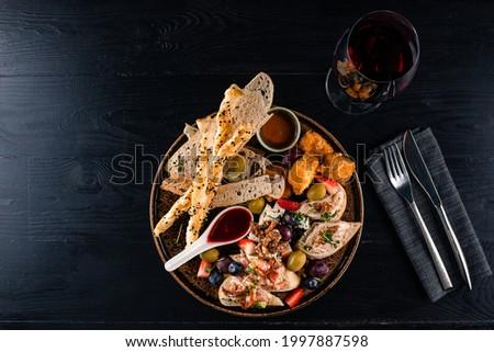 set of bruschetta and wine snacks. Italian antipasti wine snacks set. Brushettas, cheese variety, Mediterranean olives and wine in glasses over black grunge background Stock fotó ©
