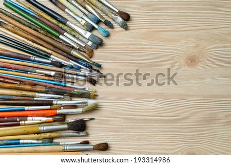 set of brushes for drawing lying on a wooden surface
