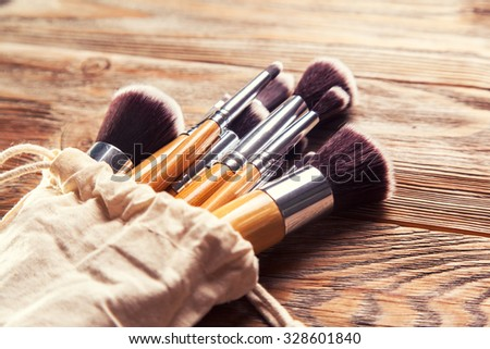 set of brushes for makeup scattered chaotically on wooden background #328601840