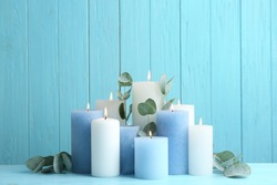 Set of burning candles with eucalyptus on table against light blue wooden background