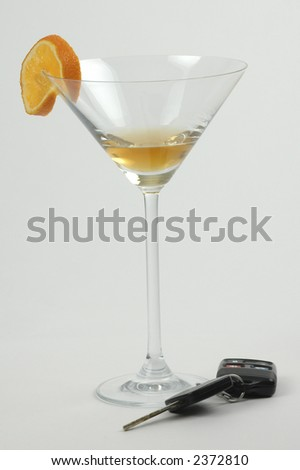 Set of car keys sitting beside an alcoholic drink.