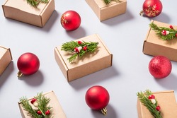 Set of cardboard boxes decorated with Christmas tree ornament on grey background