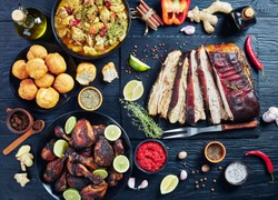set of caribbean dishes, jerk pork belly, chicken curry, fried dumplings, roasted chicken thighs and drumsticks on plates on a black wooden table with spices and herbs, view from above, flat lay
