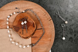Set of chain choker with pearls, earrings on a wooden stand. Trendy Jewelry. Female blog