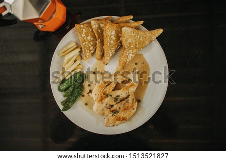 Set of chicken breast steak with garlic breads and french fries and beans.