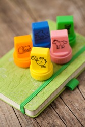 Set of children stamps and green notebook on wooden table