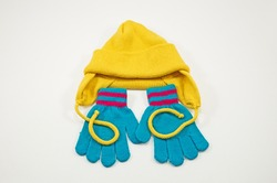 Set of childrens knitted clothes consisting of headgear and gloves isolated on a white background