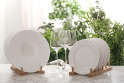 Set of clean dishware and wineglasses on white table against blurred background