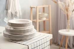 Set of clean dishware and wineglasses on white table indoors. Space for text