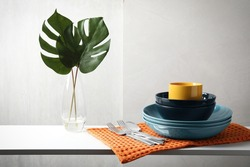 Set of clean dishware, cutlery and tropical leaves on white table