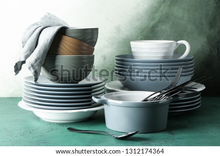 Set of clean dishware on color table