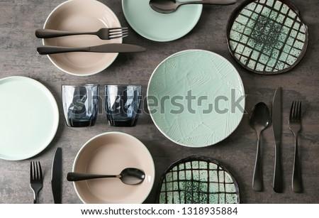 Set of clean tableware on grey background