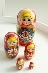 Set of closed nesting dolls on white table. Bigger and smaller similar wooden toys.