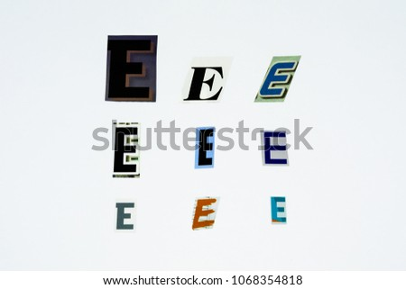 Set of collection colorful newspaper cut out letters as ornaments or design elements. Isolated on white background. Letter E.  #1068354818