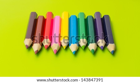 Set of colored pencils arranged in rainbow colors on olive green background