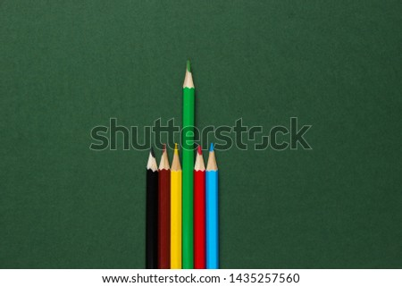Set of colored pencils on green background. Uniqueness concept.  Top view