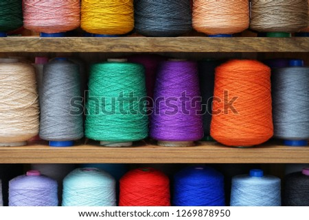 Set of colored threads for sewing on coils. Pile of big colorful spools of thread. Colored thread spools of thread large class, textiles, background