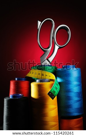 Set of colored threads in the bobbin with scissors and measuring tape