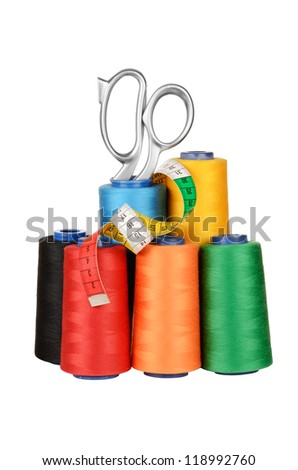 Set of colored threads in the bobbin with scissors and measuring tape. Isolated on white
