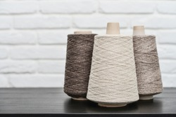 Set of colored yarn for knitting on cone on light background,  with copy space