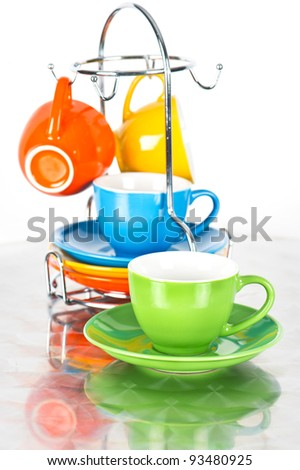 set of colorful cups with reflection. dishware. orange, blue, green, yellow