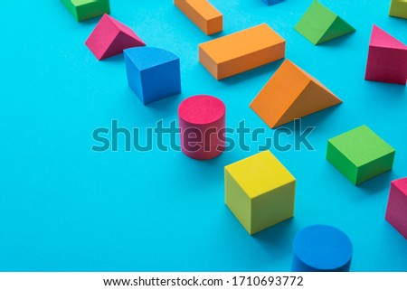 Photo of  Set of colorful geometric cube or block toy on blue background with copy space. Abstract pattern design composition by shape and form. Education, business solution and creative design product concept.