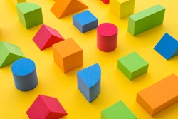 Set of colorful geometric cube or block toy on yellow background. Abstract pattern design composition by shape and form. Education, business solution and creative design product concept.