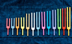 set of colorful metal tuning forks, sound healing and acutonic tools in order of size increase
