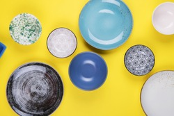 Set of colorful modern porcelain plates and bowls on a yellow background. designer ceramic bowls in different colors stacked together. Blue, turquoise, grey and dark blue bowls. Top view