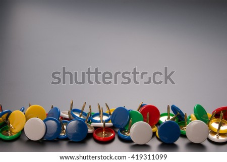 Set of colorful office push pins on black background with copy space. Group of colorful office push pins on black paper background with copy space. Close up of office push pins.