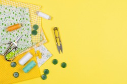Set of colorful yellow and green fabrics, scissors, buttons, spools of thread and glasses on yellow. Concept for tailoring,  patchwork and handwork.  Needlework and Sewing.