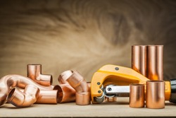 set of copper pipe fittings and  pipe cutter on vintage wood background