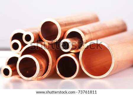 Set of copper pipes of different diameter lying in one heap