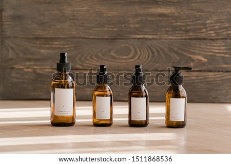 Set of cosmetic dark amber glass bottles on wooden background. Closeup, copyspace. Beauty blogging, salon treatment concept, minimalism brand packaging mock up