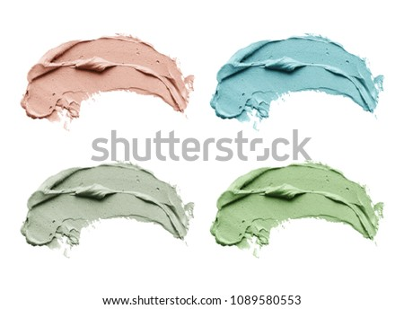 Set of cosmetic mud mask smears isolated on white background. Top view, closeup texture of blue, red and green facial clay, copy space