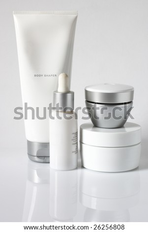 Set of cosmetic products in white and grey containers on light background.
