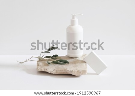 Set of cosmetic products on light background. White plastic pump bottle for shampoo, lotion mockup on stone podium. Blank soap box. Green olive tree branch. Healthy cosmetology, spa treatment concept. Foto d'archivio ©