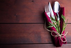 Set of cutlery knife, spoon, fork. Сutlery with burgundy napkin and twine. Rosemary on wooden background. Copy space. Top view