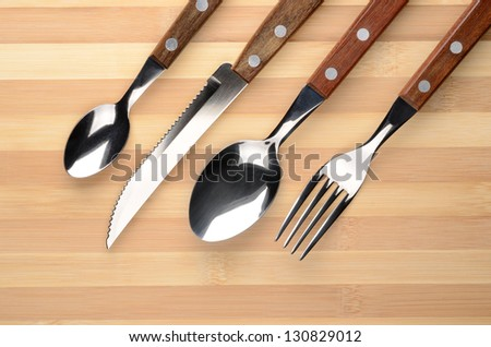 Set of cutlery on a wooden table. Knife, fork, spoon.